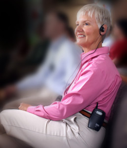 "Title: Photo of a Lady Using an Assistive Listening Earspeaker - Description: A woman, wearing a pink shirt and khaki pants, is smiling while wearing a wireless assistive hearing device called an ""FM system."""