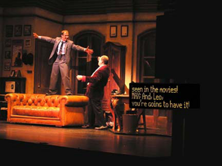 On the left side of a stage, a man stands on the back of a couch and gestures wildly to another man looking up at him.  On the right side of the stage, displayed on a short black screen, closed captioning is provided for an audience at a live theater show.