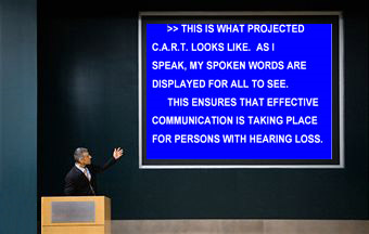 "A man in a suit stands at a podium and gestures to a large blue screen behind him.  On it, CART is provided for an individual with hearing loss.  The words on the screen are ""This is what projected CART looks like. As I speak, my spoken words are displayed for all to see. This ensures that effective communication is taking place for persons with hearing loss.""Image courtesy of Caption Crew."