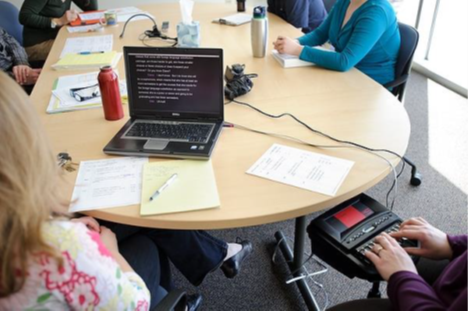 Several people are sitting around a table.  At one end of the table, CART is being provided for an individual with hearing loss on the individual's personal laptop at a work meeting.