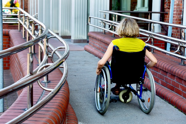 A woman pushing herself in a wheelchair in front of a building