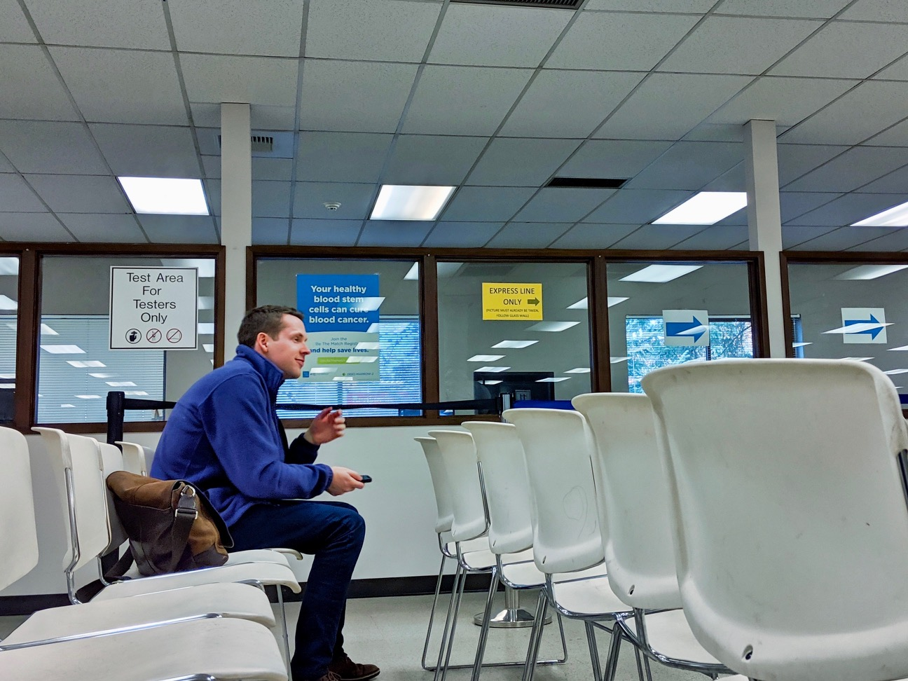 A man sitting inside a DMV office