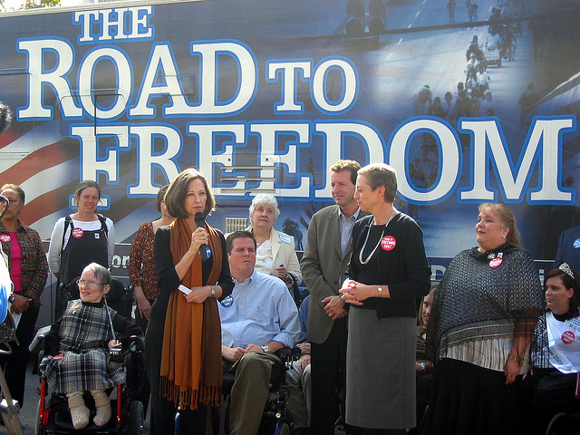 Susan Edwards, Frist Center Executive Director and CEO, speaks to visitors, joined by Carol Westlake, Tennessee Disability Coalition Executive Director, and Jim Ward, with the Road to Freedom bus tour