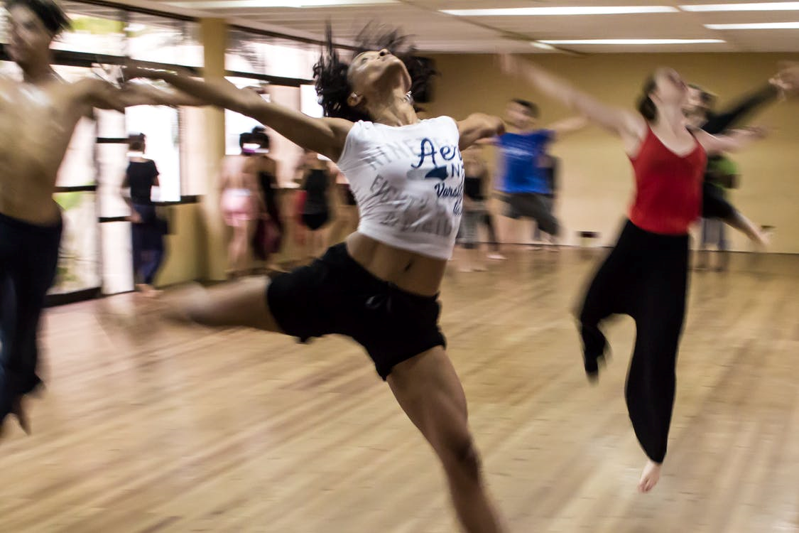 A blurry image of a group of women and men mid-movement, dancing in a dance studio.