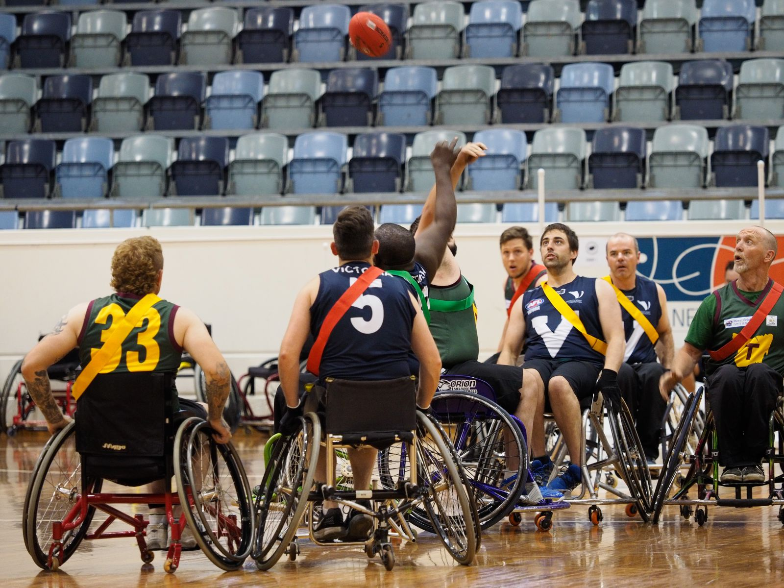 American football players in wheelchairs on an indoor court