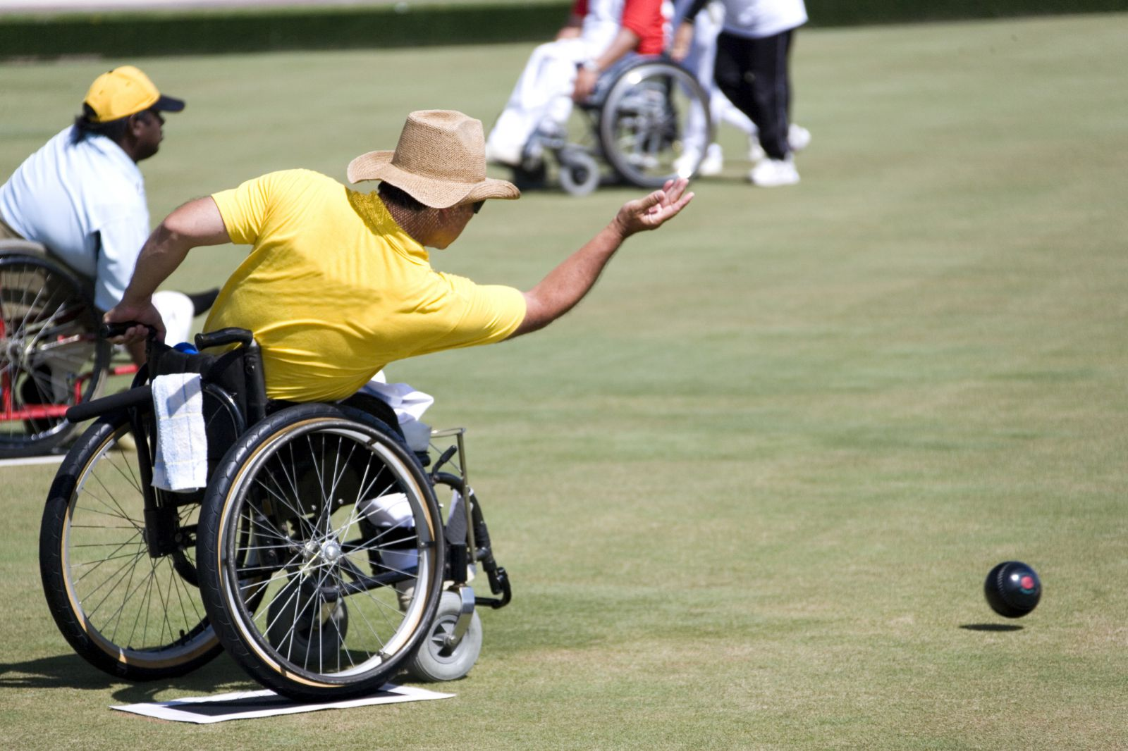 A man wearing a yellow shirt and a tan cowboy hat leans forward in a wheelchair, throwing a large, black ball across a lawn bowling playing field.