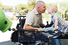 Man in wheelchair smiles at his young son as he plays on a playground.