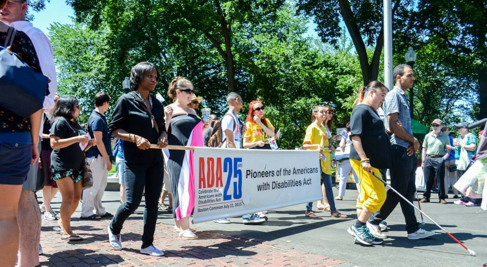 People march in the ADA Anniversary parade holding a banner reading ADA 25 Pioneers of the Americans with Disabilities Act