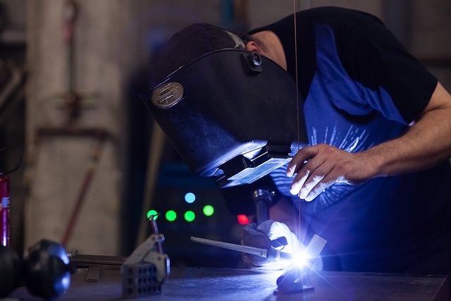 Person wearing a welding helmet using welding equipment to fuse two pieces of metal together. This image is for illustrative purposes only and does not depict individuals in the story.
