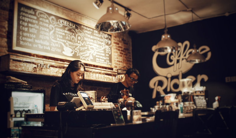 In a dark, cozy coffee shop with items on a chalk board, a female barista is behind the register while a male barista is preparing a drink. This image is for illustrative purposes only and does not depict individuals in the story.