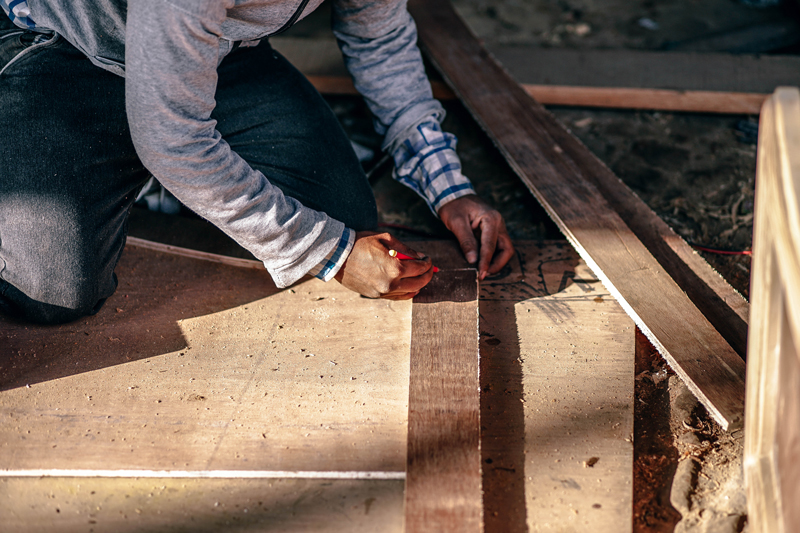 Person kneeling and marking a piece of lumber before cutting it on a construction site. This image is for illustrative purposes only and does not depict individuals in the story.