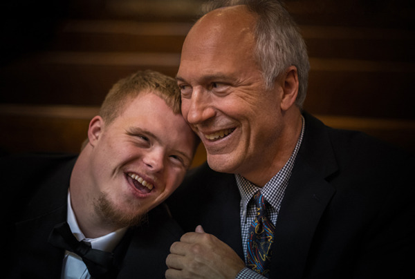 A young man with down syndrome hugs and laughs with an older gentleman: his father. To protect the privacy of individuals involved, people represented on this photograph are not the ones depicted in the story